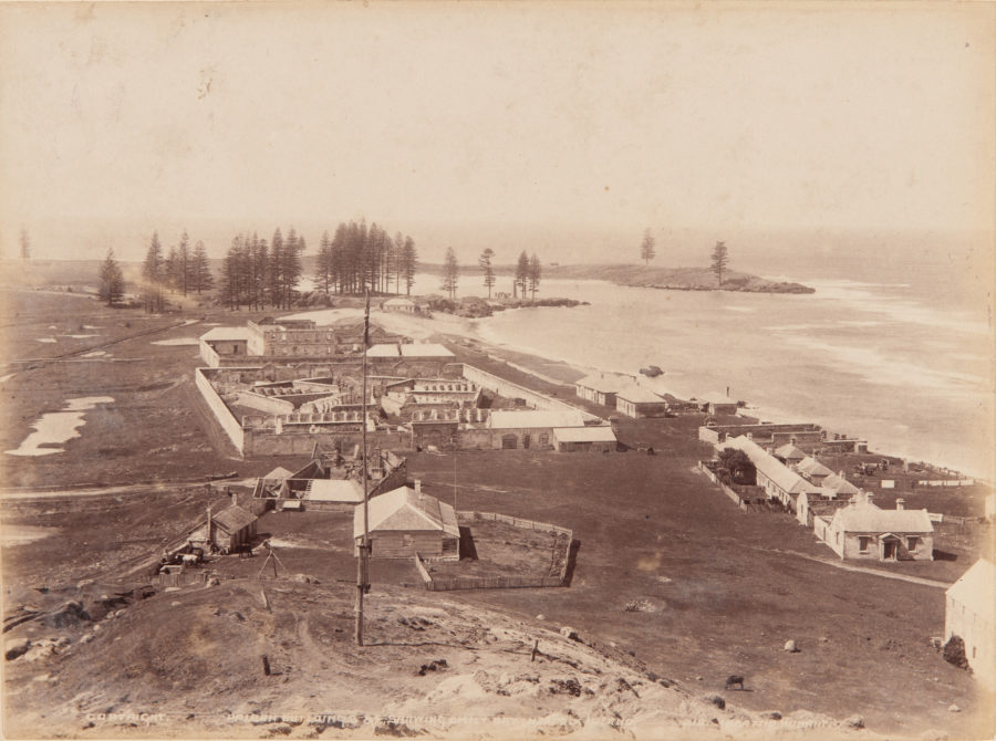 Brown toned photo of sandy landscape with sandstone prison buildings and distant trees with bay to right.