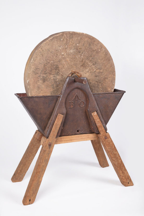 Stone wheel set in metal and wood stand with metal and wood turning handle. Letters in relief on metal stand B' and 'O' with an arrow above them.