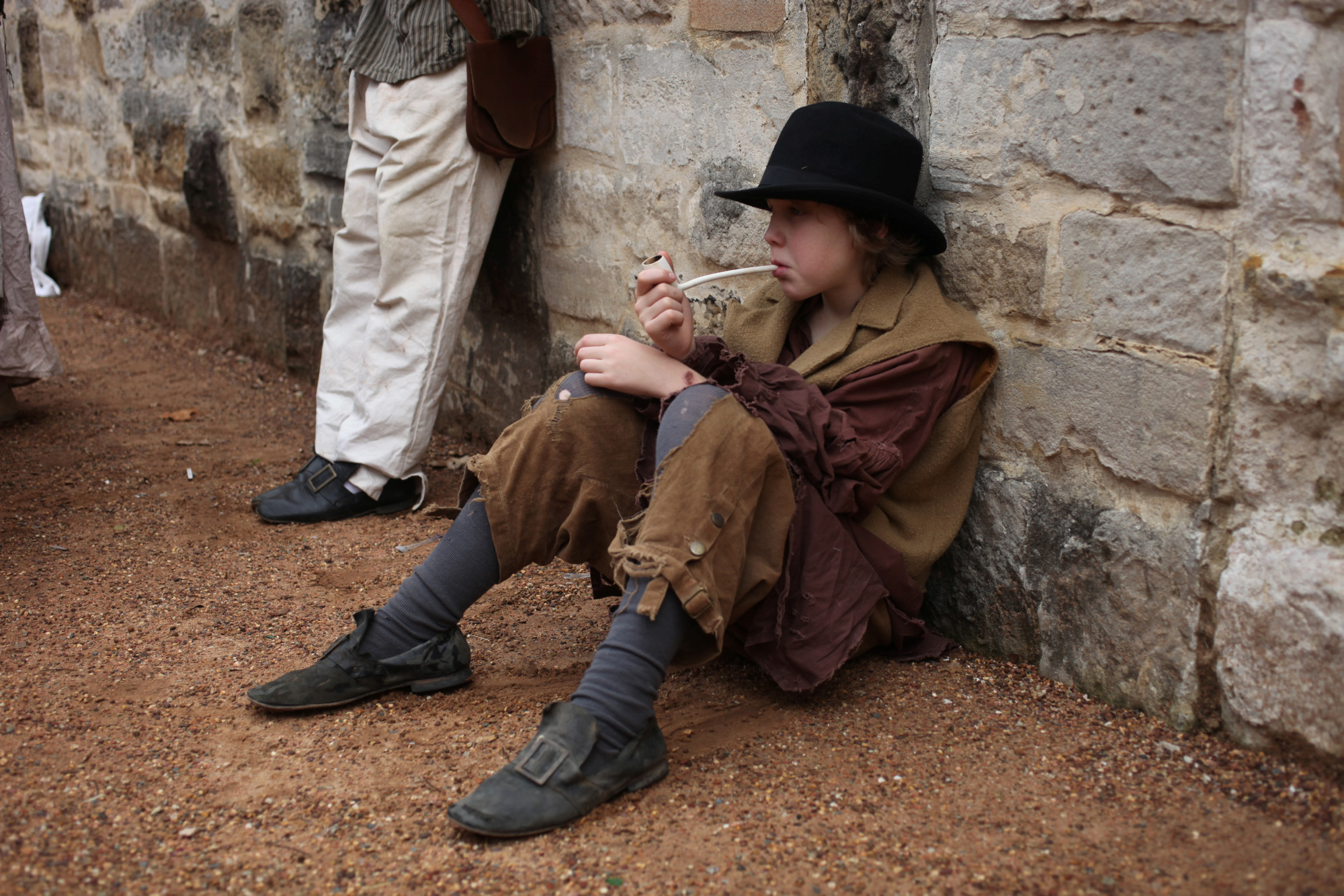 Child dressed as convict slumped against stone wall 'smoking' a pipe.