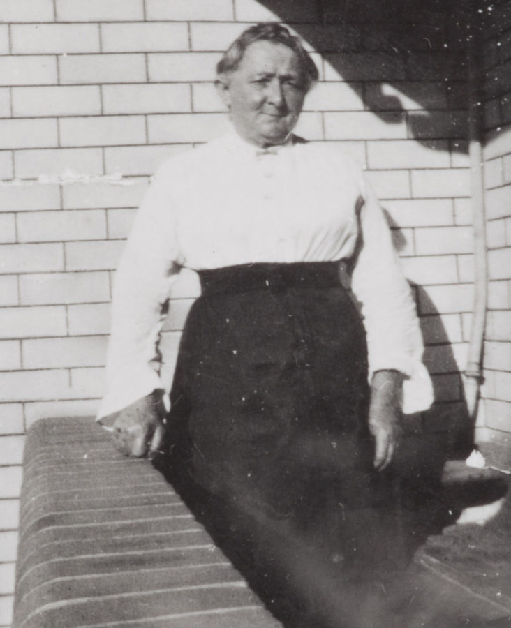 Severe looking woman in white blouse and dark high waisted long skirt, leaning on low brick wall on balcony.