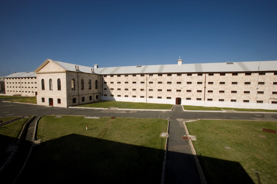 Long pale coloured cell block of old jail with green grass in front.