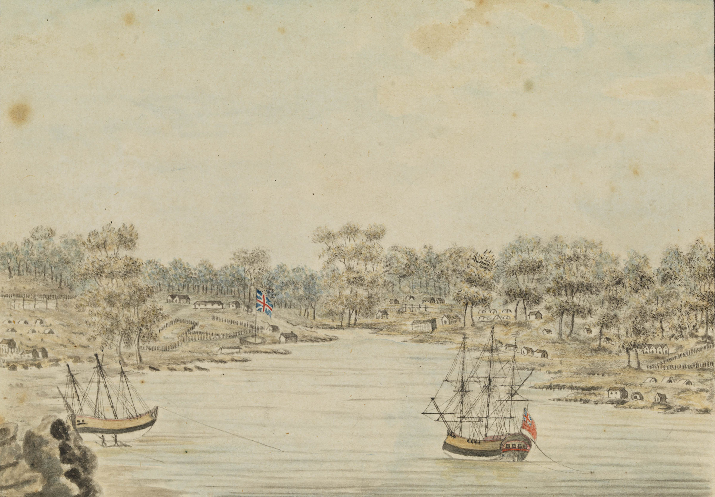 Two of the ships of the first fleet in Sydney Cove. A scattering of huts and tents can be seen amongst the trees and on the slopes rising beyond the British Union Jack stood the Governor Phillip's portable home and colonial headquarters.