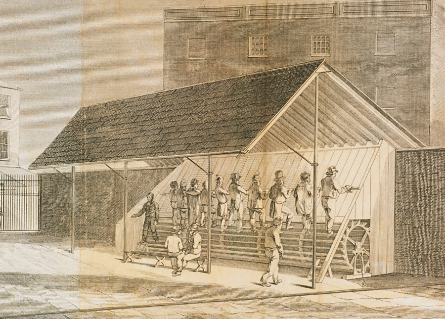 Open sided shed with men in a row, walking on long cylinder, with other men looking on from yard.