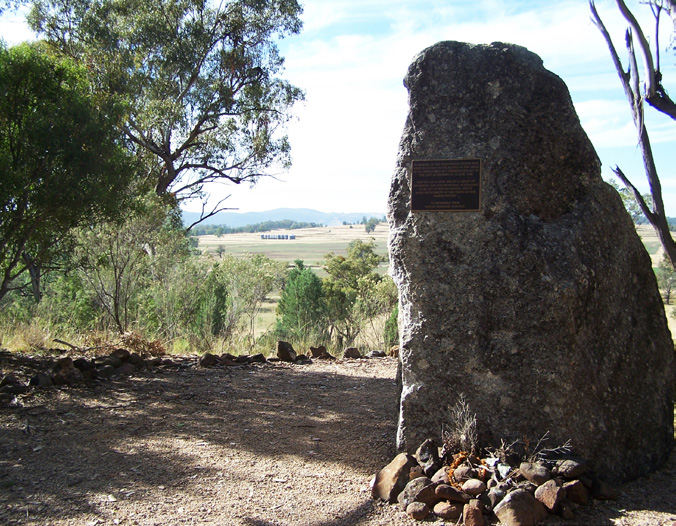 Stone monument with plaque with distant view behind.