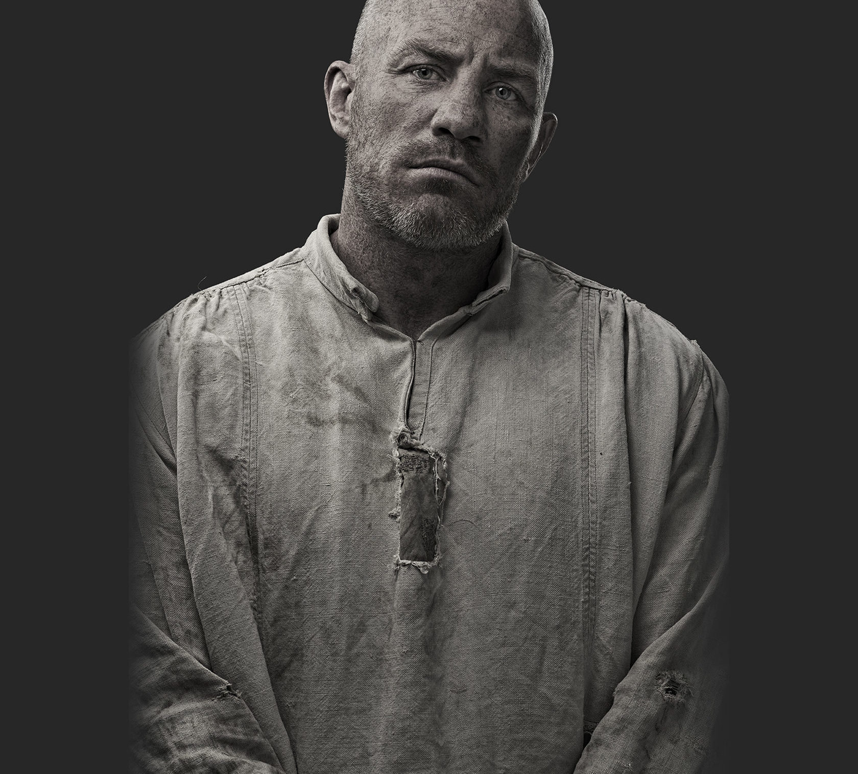 Bald man dressed as convict with black background.