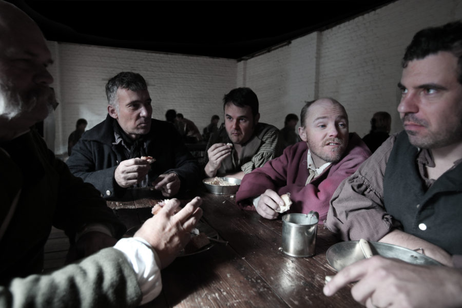 Group of men sitting around table with food and metal mugs of drink.