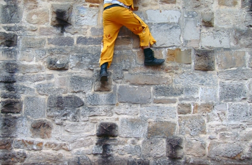 Pair of legs clad in pants and boots, dangling from top of sandstone wall.