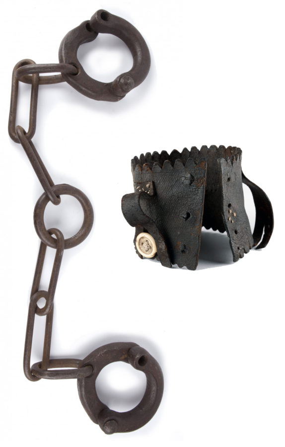 Heavy iron rings connected by chain, with hand tooled leather cuff with large white button and strap.