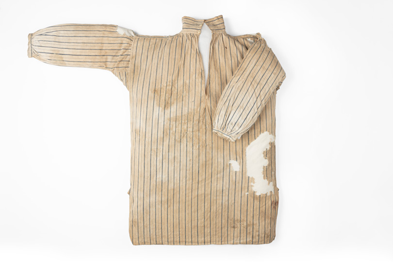 Worn striped shirt with one arm folded in.