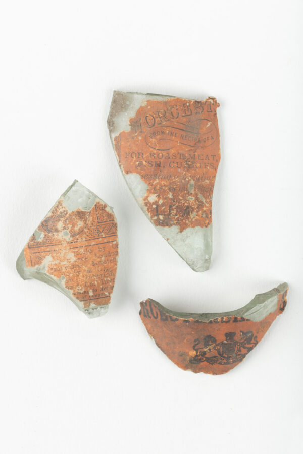Three bottle fragments with red label from Worcestershire sauce bottle.