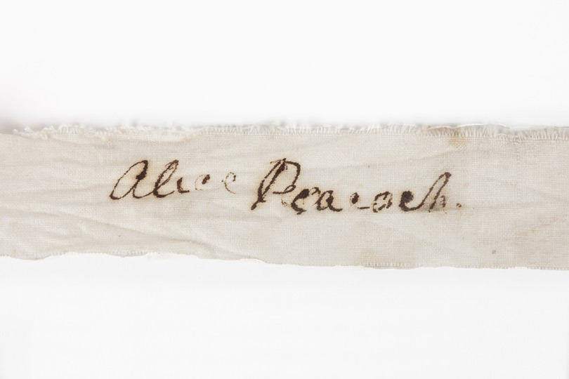 Detail from rectangular cotton fragment with 'Alice Peacock' handwritten in cursive style.