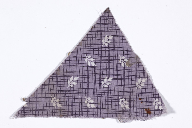 Triangular scrap of purple fabric with leaf motif on checked pattern.