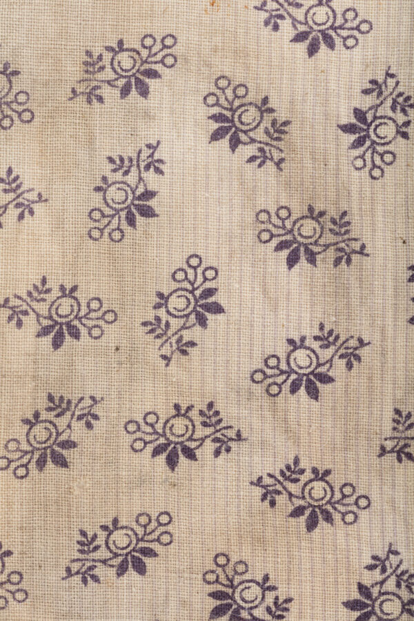 Rectangle of cloth with purple floral motif.
