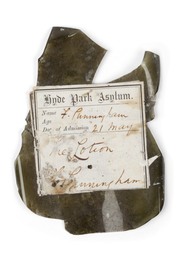 Bottle with label attached over earlier label, Hyde Park Asylum Dispensary, excavated from beneath the floorboards of Hyde Park Barracks