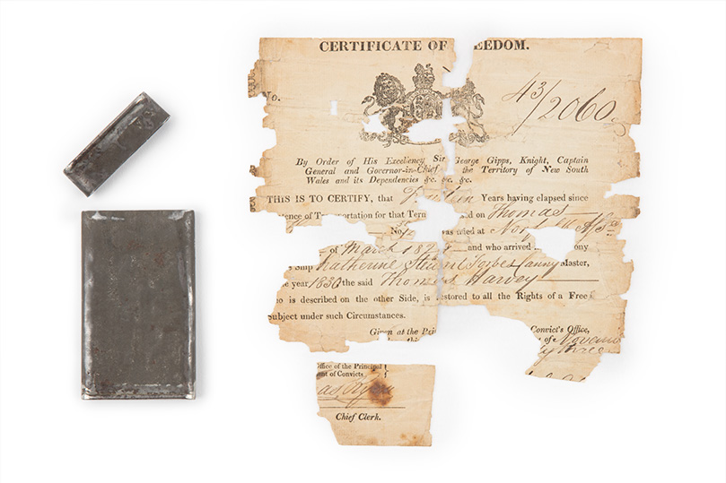 Fragmented paper certificate with metal tin to left.
