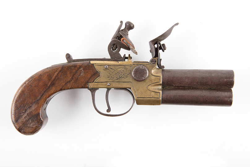 Wooden handled pistol with brass plate.
