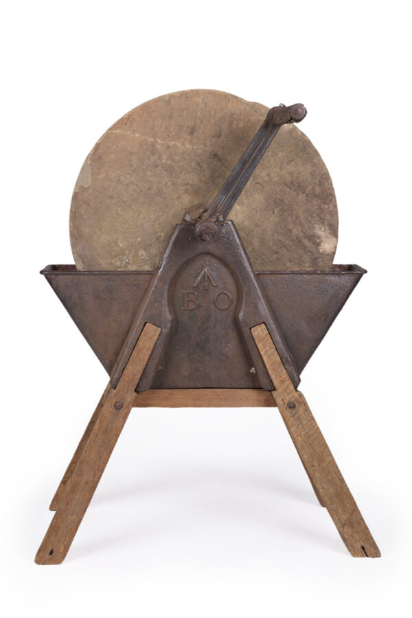 Circular stone wheel housed in metal and wood stand with a turning handle.