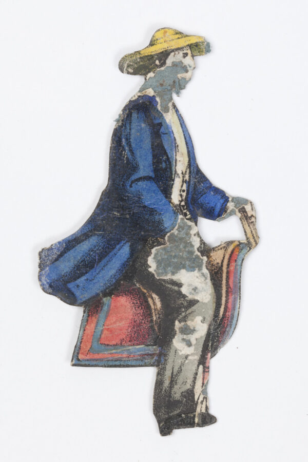 Cutout image of man in blue coat and yellow hat sitting on saddle.