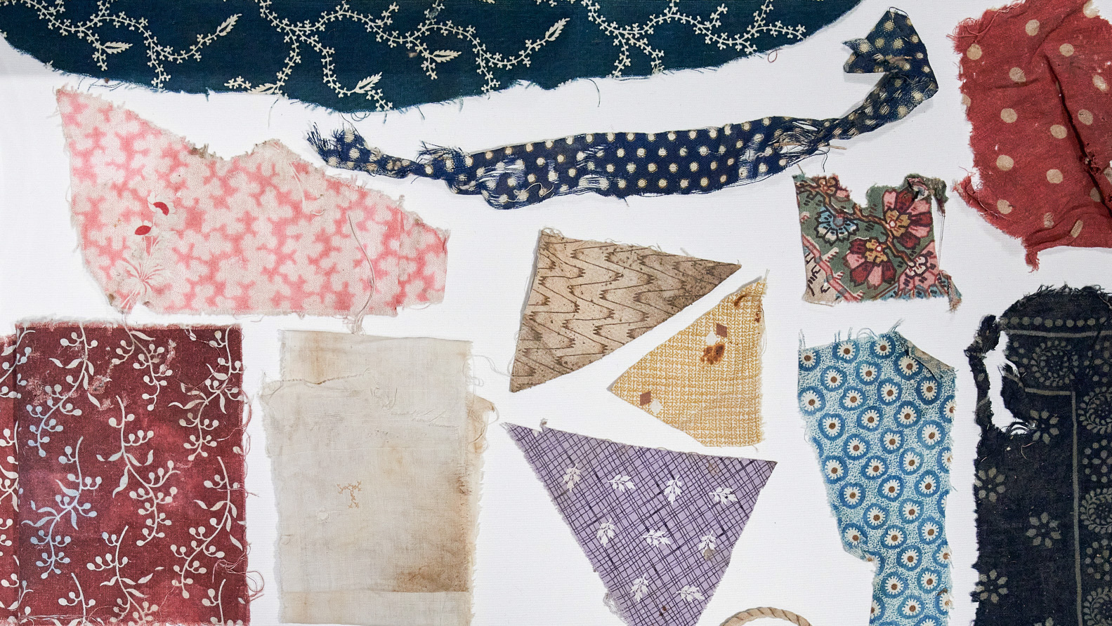 Variety of shapes, colours and patterns of fabric offcuts.