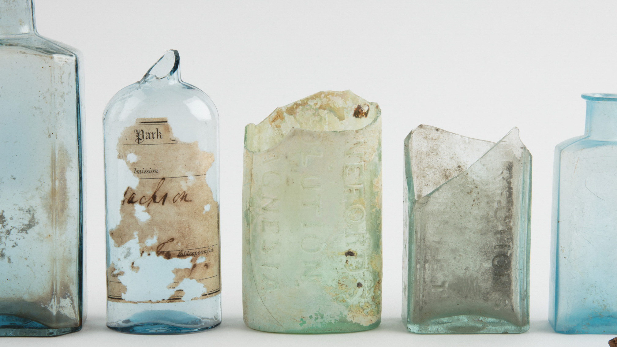 Assorted bottles, broken and whole and stoppers