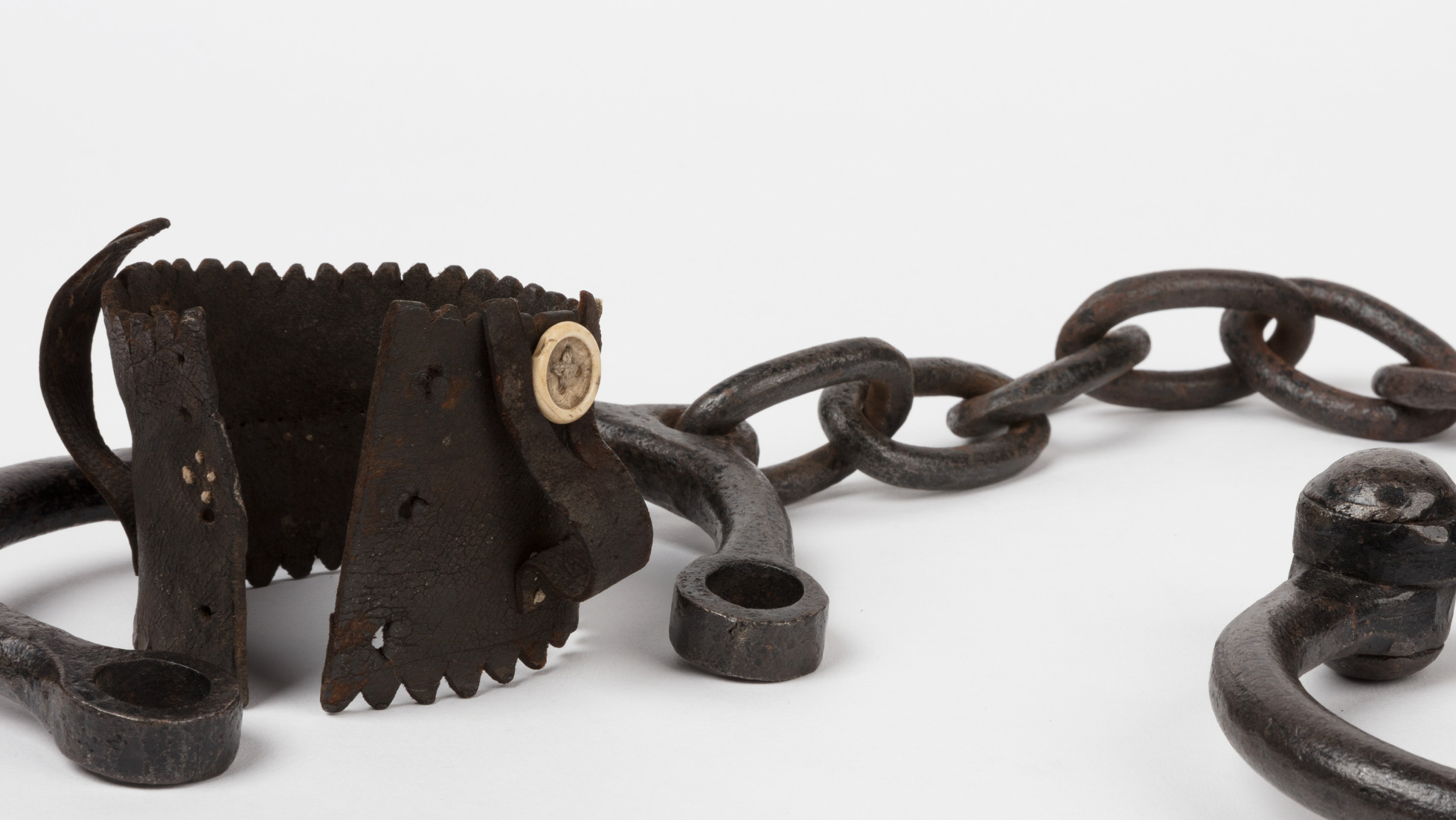 Metal shackles with handmade leather cuff with button fastening.