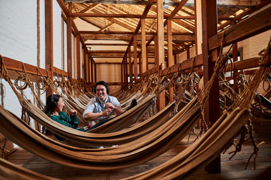 Long open raftered room strung with hammocks, with two people in centre of photo.