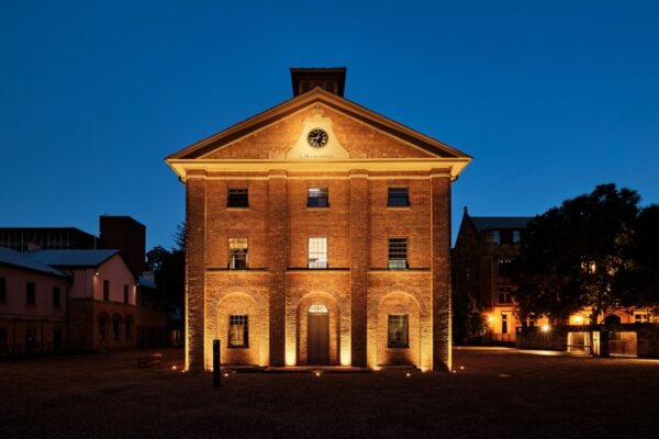 Two-storey brick building in gravel courtyard lit up for night time.